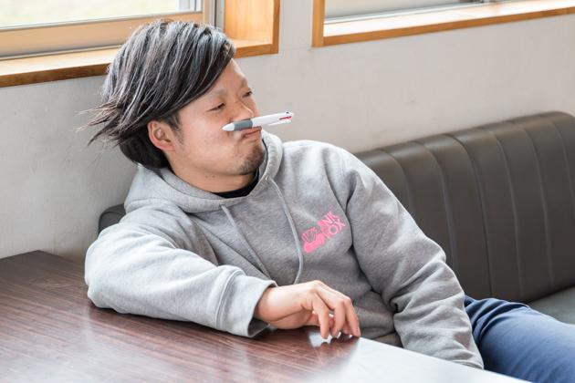 唇の上にボールペンを乗せて、退屈そうにしている写真