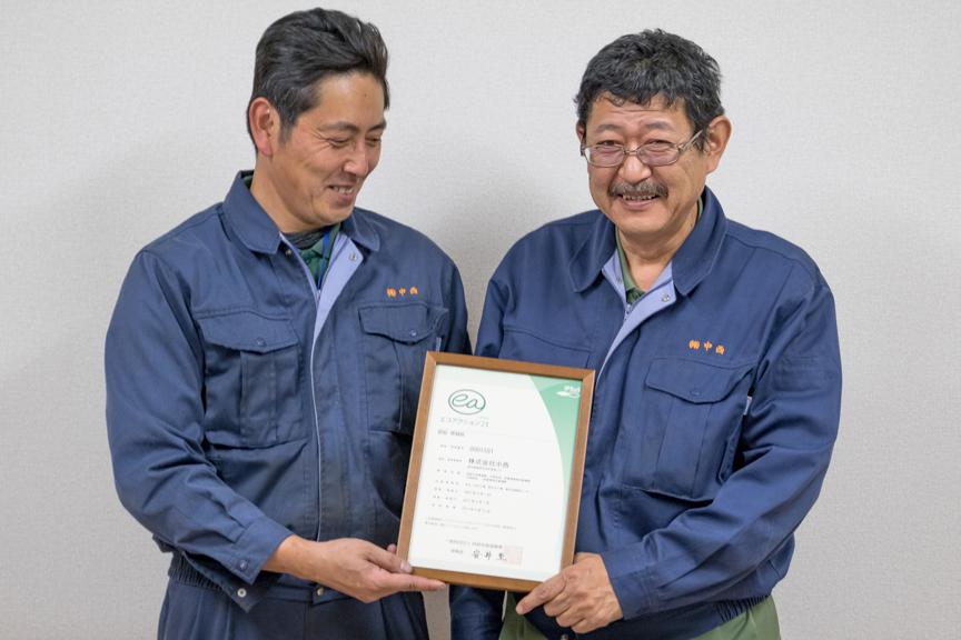 エコアクション21の認定証と担当社員の写真